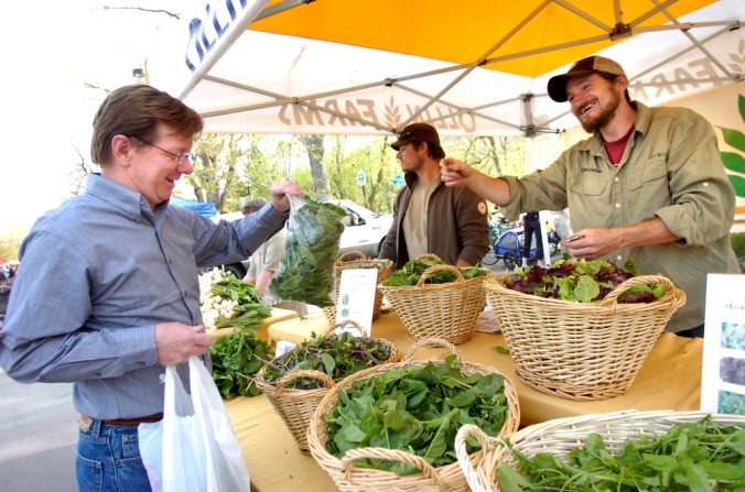 FARM MARKET.jpg Mark Guttridge, of Ollin Farms, at right, passes on a bag of fresh spinach to Steve Toon on the first Wednesday night of the Boulder Farmers' Market in 2010. Toon from Golden, works in Boulder and considers going to the market his hobby. Photo by Paul Aiken / The Camera / May 5, 2010.